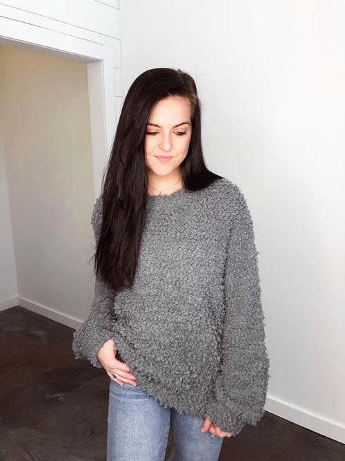 A young woman in a fluffy grey sweater