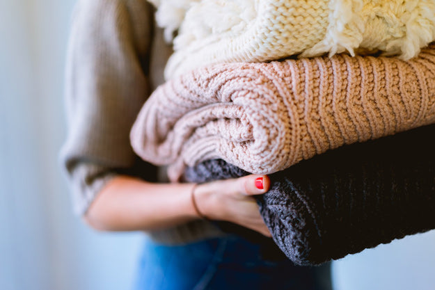 woman holding pile of sweaters