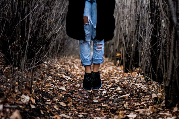 woman in forest surrounded by autumn leaves wearing DIY distressed jeans and black sneakers