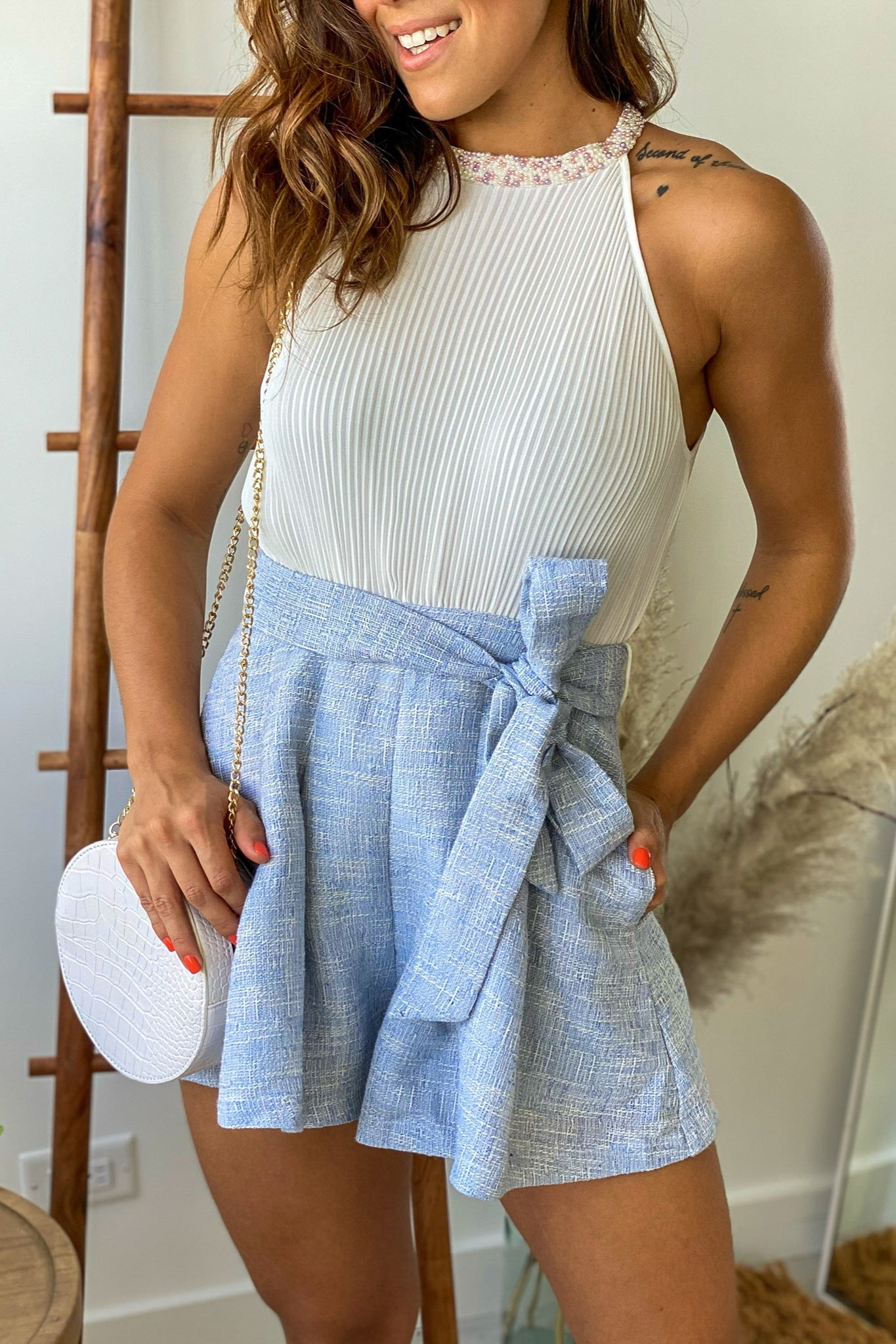 blue and white sleeveless romper with embellished neck