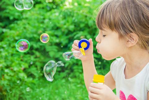 A little girl is blowing bubbles in front of a bush