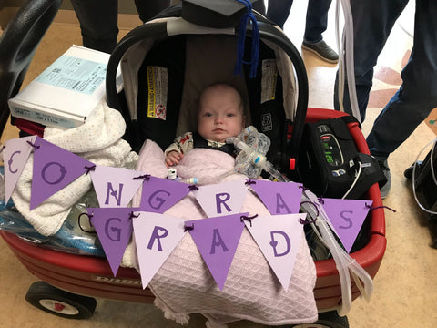 "Baby Lily is in a baby carrier with a banner that says ""CONGRATS GRAD"" on her last day in the NICU"