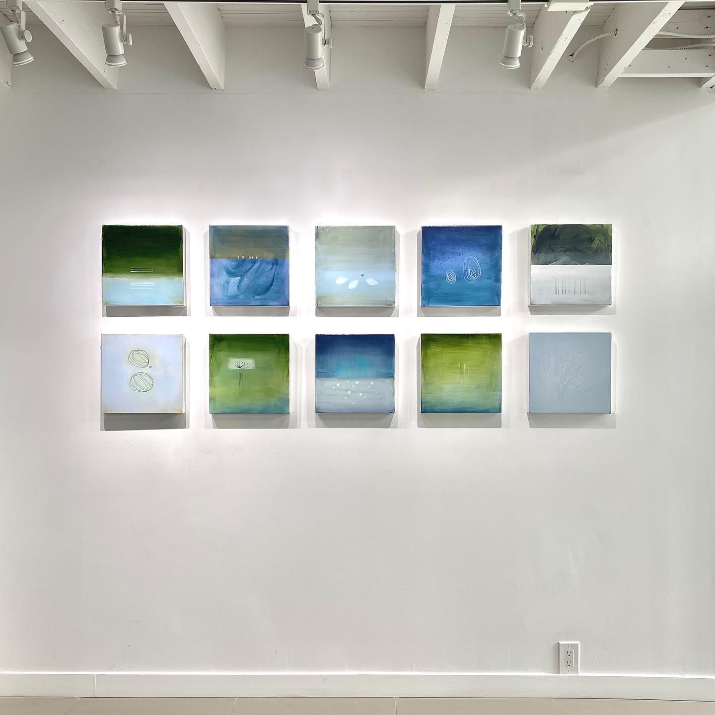 A wall of small paintings by Janet Taylor inside the Quiet Stores Exhibition.