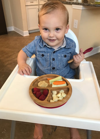 Young toddler boy with short hair smiling holding a bamboo spoon with a magenta silicone one one end. Toddler is sitting in his white high chair and has an Avanchy Bamboo plate in front of him full of healthy snacks.