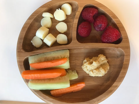 Avanchy's round bamboo plate. There are three separate sections in this plate. One section contains sliced cheese, the second section contains raspberries, the last and largest section holds cucumber and carrot spears with hummus.