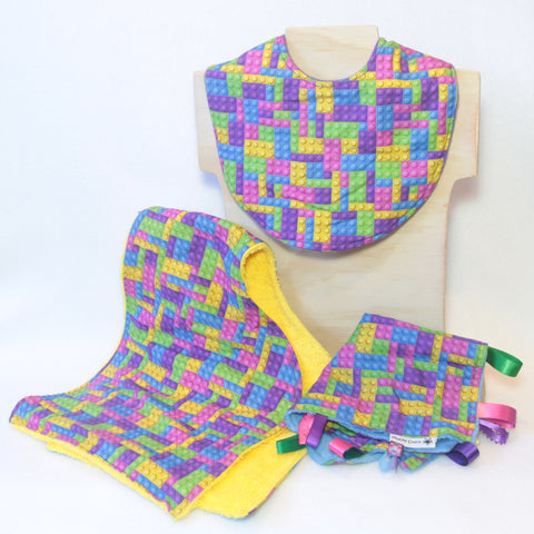 Mucky Duck Crafts blue pink purple and yellow building blocks gift pack containing regular dribble bib burp cloth and sensory cloth taggy