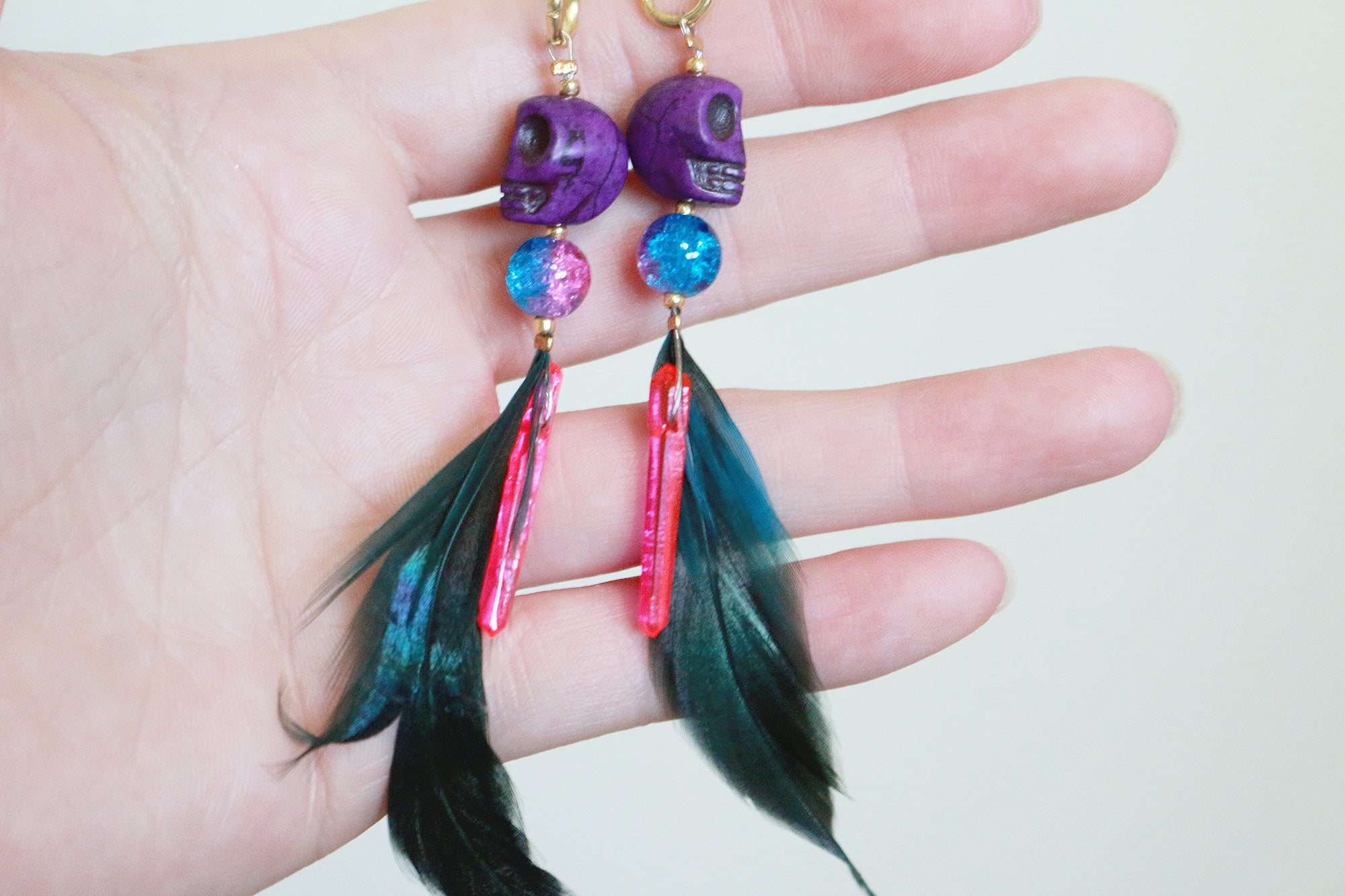 Pink crystal howlite skull feathered earrings