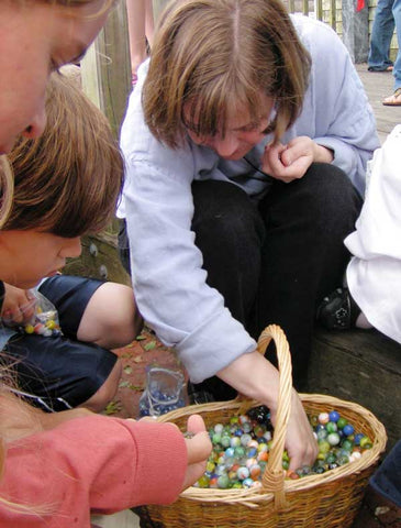 Loren and children pick out marbles from a basket