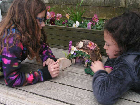 Two young girls playing with a fairy house