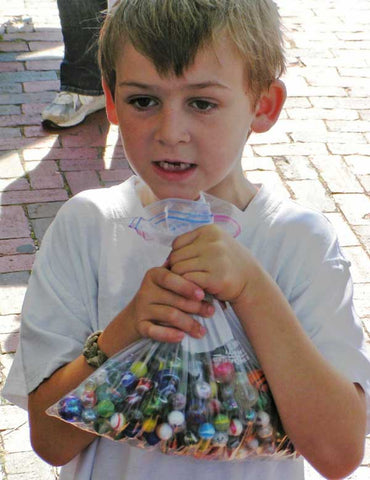 A little boy holding a bag of marbles