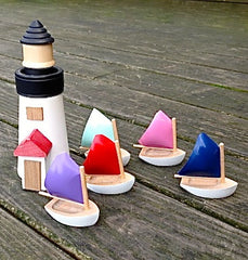 "A set of six wooden ""Rainbow Fleet"" sail boats with the Brant Point Lighthouse"