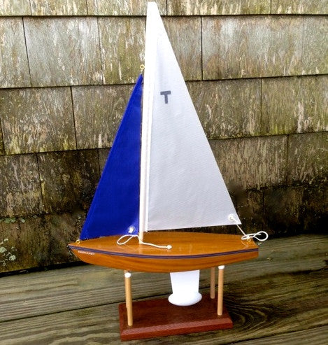 "Hnad made 12 inch letter ""T"" sail boat with a blue and white sail."