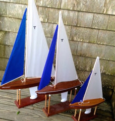 "Three handmade sail boats with the blue and white sails showing hte letter ""T"""