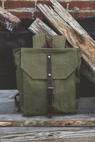 Olive green cotton backpack with brown leather strap