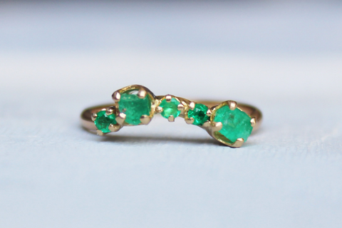 gold ring with several raw emerald stones
