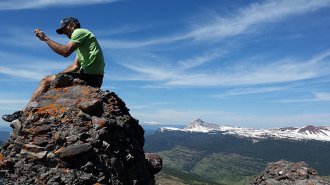 SOM owner Olie Marchal sits atop a mountain in his favorite sneakers.