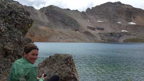 SOM Footwear co-founder Nathalie Bouchard sits by a lake in the colorado backcountry.
