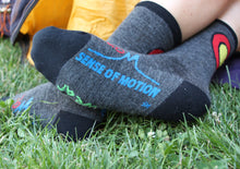 Merino wool colorado made socks on feet showing logo on sides of foot and Colorado C on back of ankle