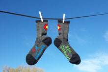 Merino Wool Colorado made socks hanging from clothesline. SOM Footwear logo on foot, Colorado flag at back ankle