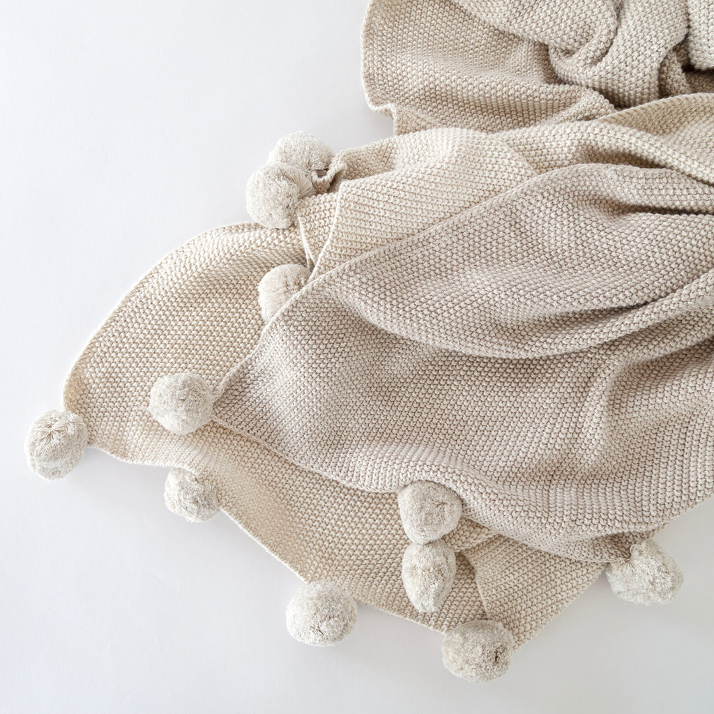 Birdie Throw,Natural Ombre, a beige knit blanket throw with pom poms from Tonic Living