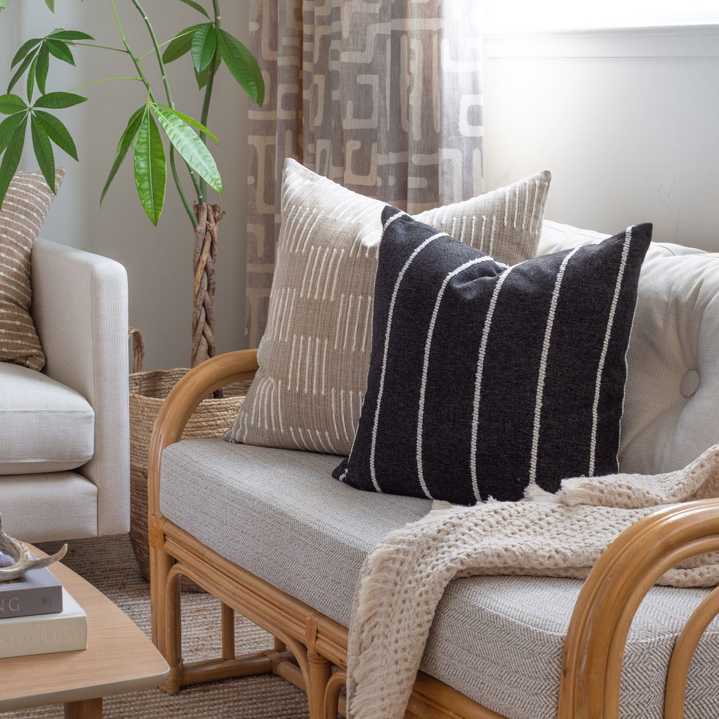 neutral decor: black and white vertical stripe pillow and burlap beige and cream pillow on a rattan love seat