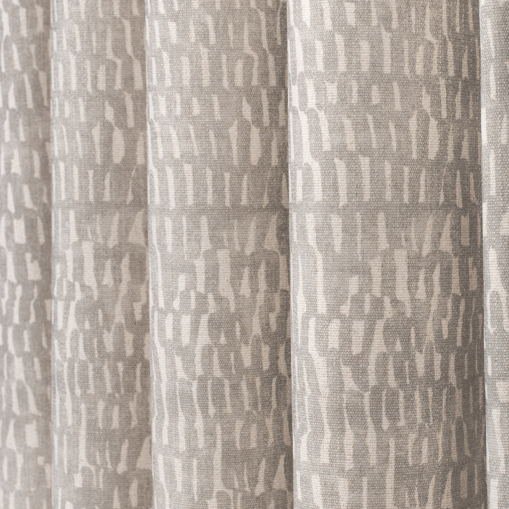 Avareno Silver, a light grey and sandy beige small scale abstract print fabric : close up draped view