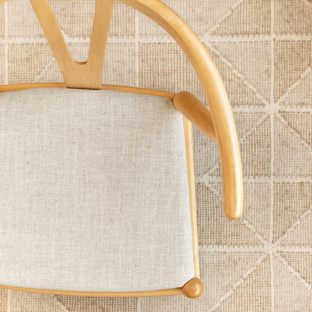 Benton parchment, a beige home decor fabric shown on a chair seat