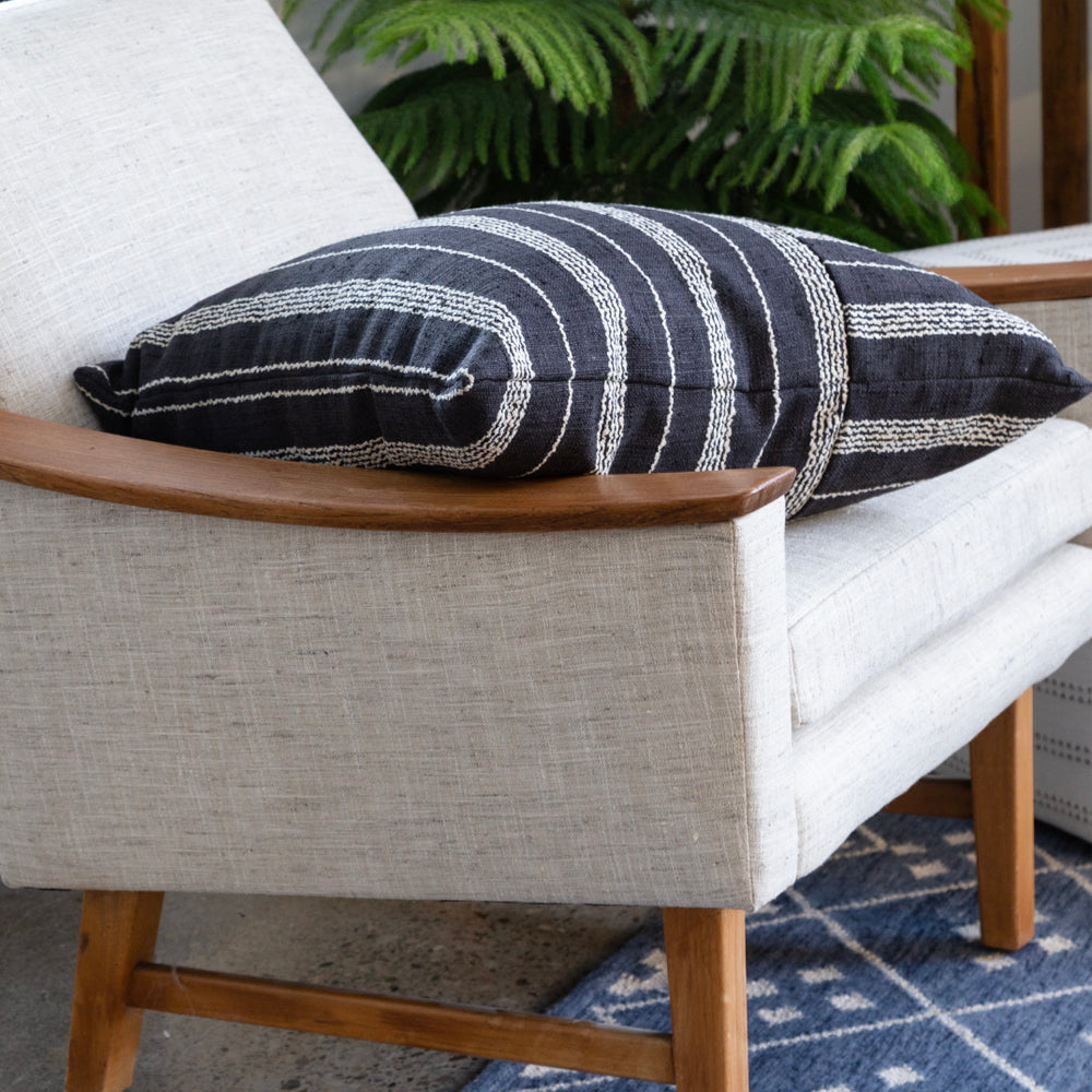 black and white stripe pillow on arm chair