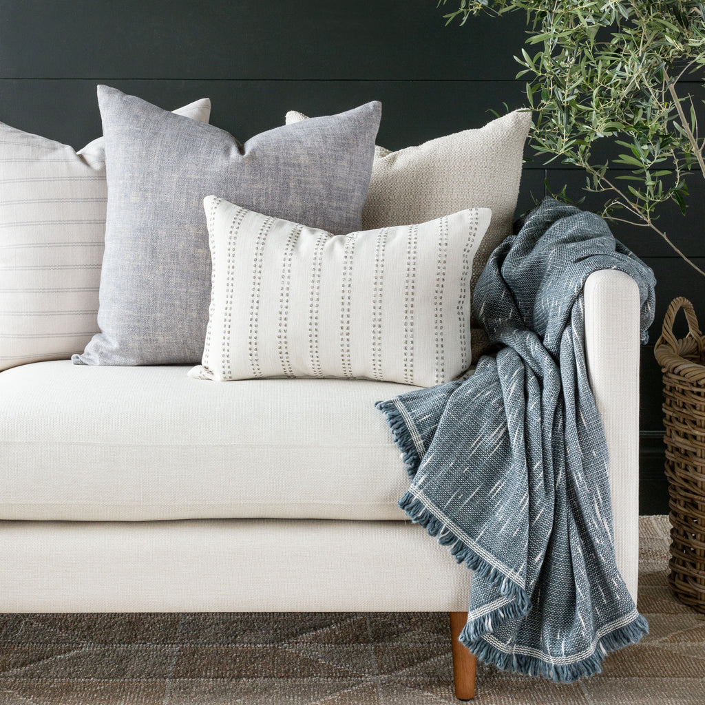 Elodie lumbar pillow combo with Quinto Shadow, Farina Birch and Milly Vanilla pillows and Rafael blue throw on a cream sofa