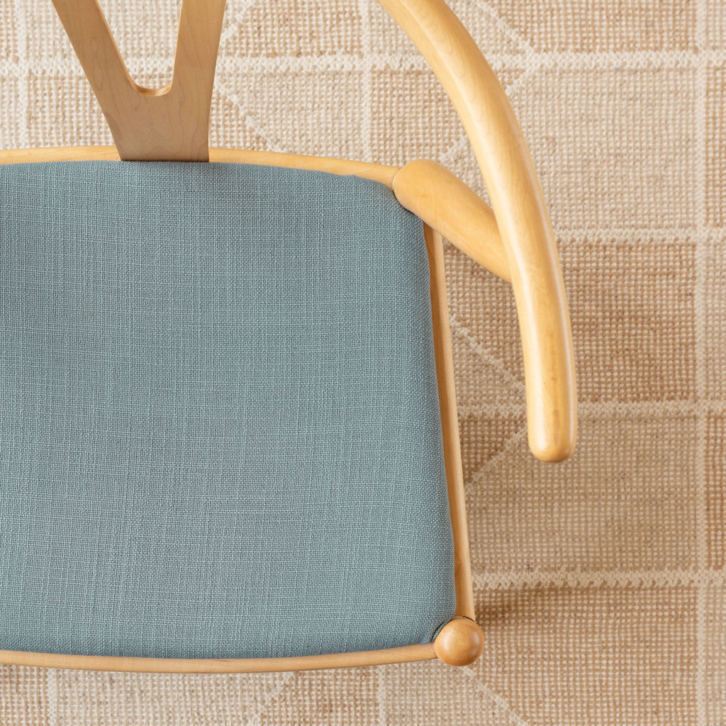 Grange Seaspray, a watery blue high performance upholstery fabric shown on a chair seat