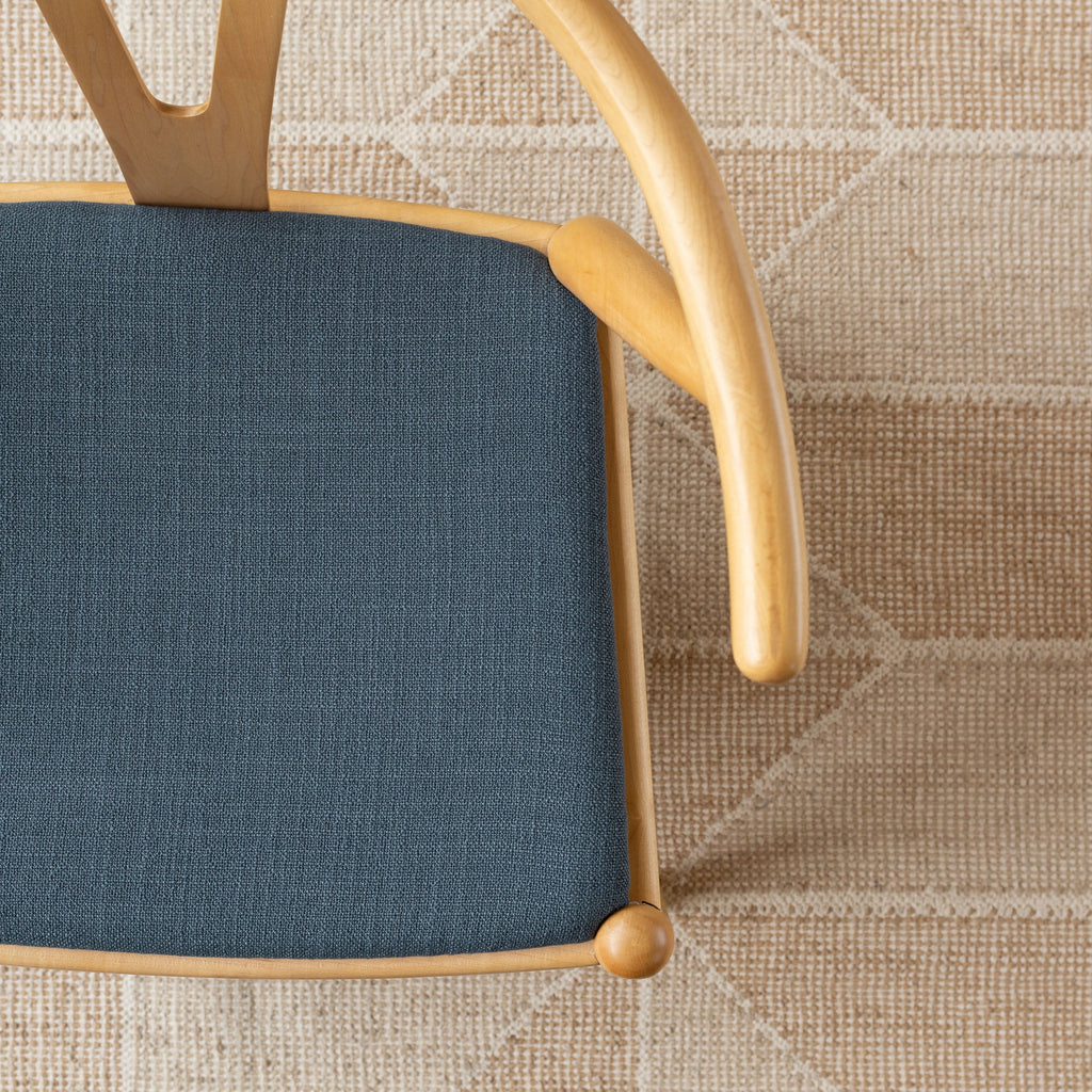 Grange Fabric Storm Blue, a high performance denim blue upholstery fabric shown on a chair seat