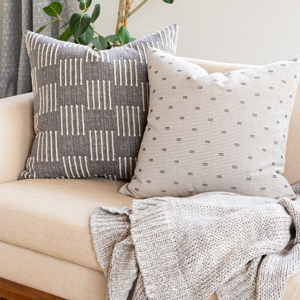 grey, black and white striped pillow combination on sofa