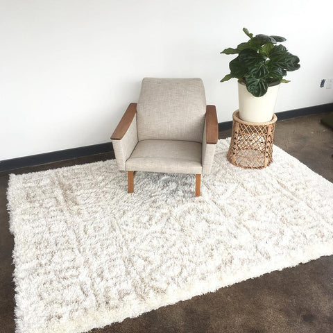 Hora - A cozy shag rug in a soft and natural palette of cream and oatmeal-tan in a aztec pattern.