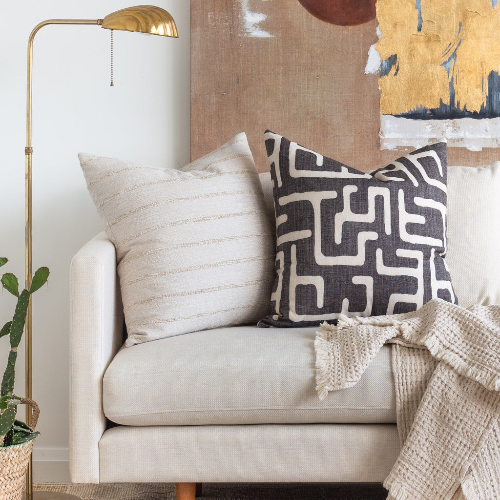 Boho Decor: Handlavet beige textured stripe pillow and Karru Charcoal print pillow on a sofa