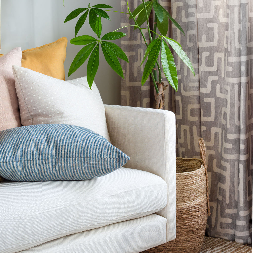 Lifestyle photo:colourful pillows on a sofa and  Karru kuba inspired grey and cream print drapes