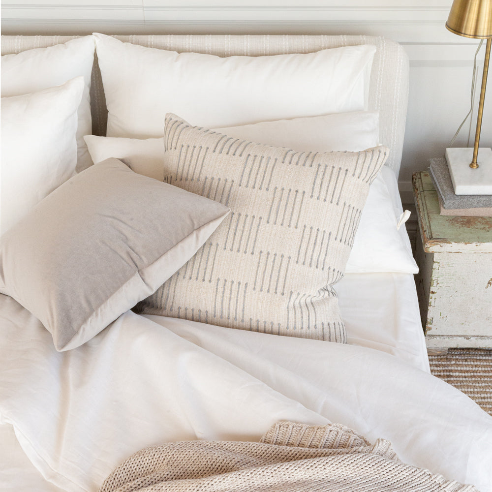 gray velvet and beige pattern pillow on a bed