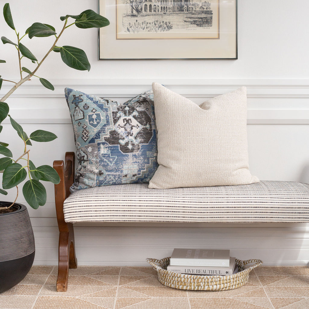 Home decor vignette: Milly cream pillow with Saro blue tapestry pattern pillow on Misto cream and black stripe fabric bench