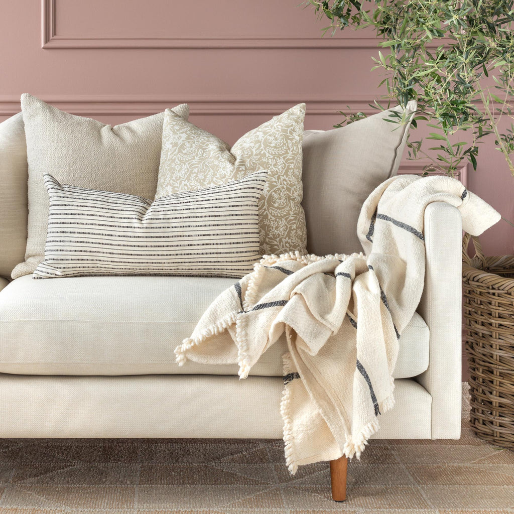 Neutral pillow combination with Misto cream and black lumbar pillow shown on a cream sofa