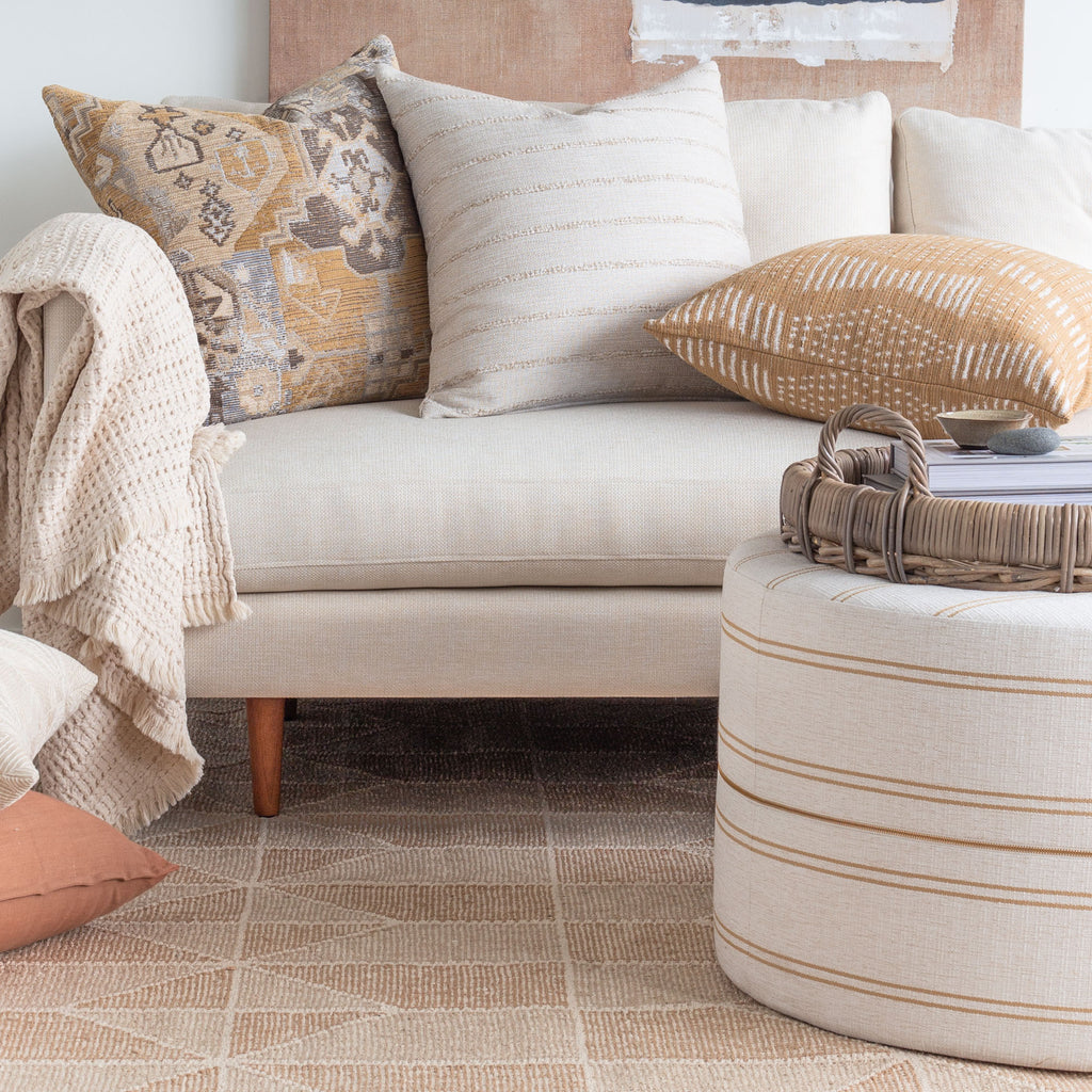Living room vignette: Oud Cork round ottoman shown with earth tone sofa pillows and rug