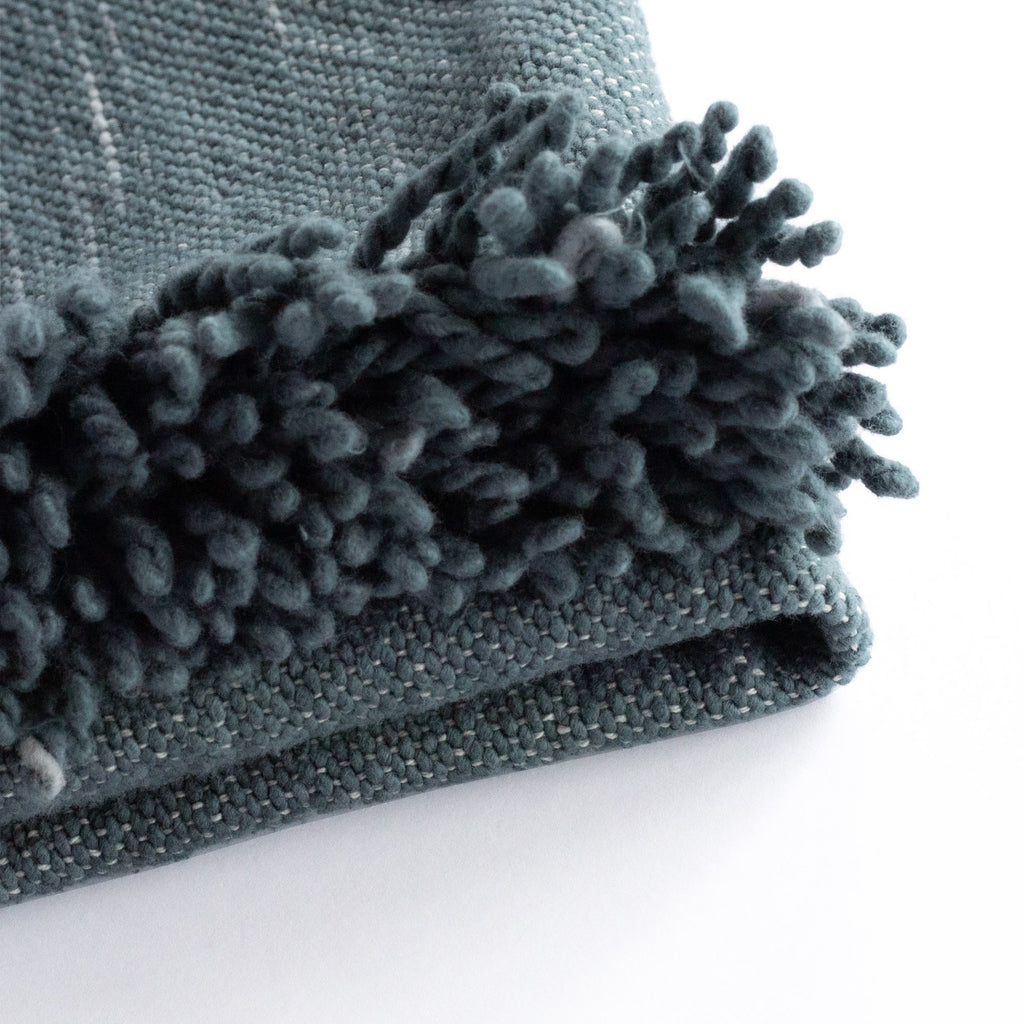 Rafael Stone Blue, a deep blue with cream slubs, chunky weave cotton throw blanket : close up of fringe edge