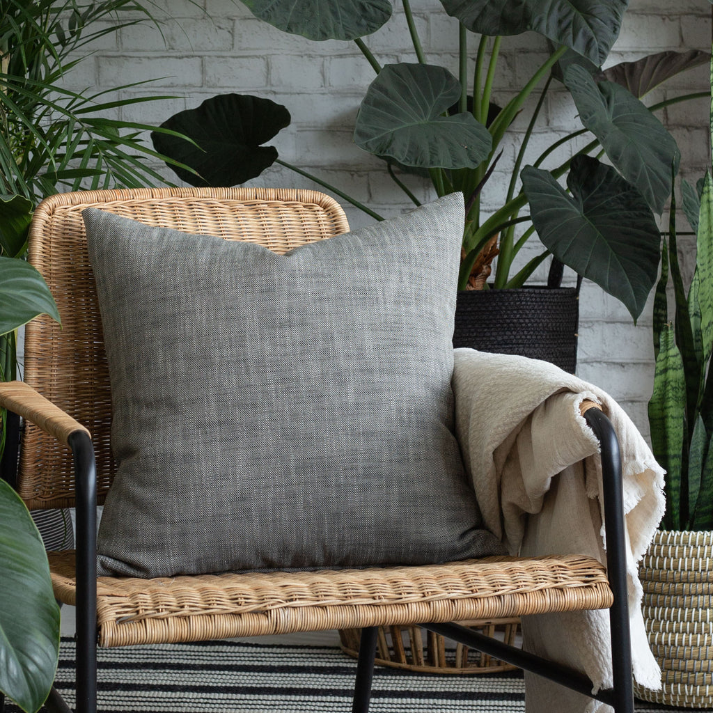 Ryder Mink charcoal tone pillow on a chair surrounded by plants