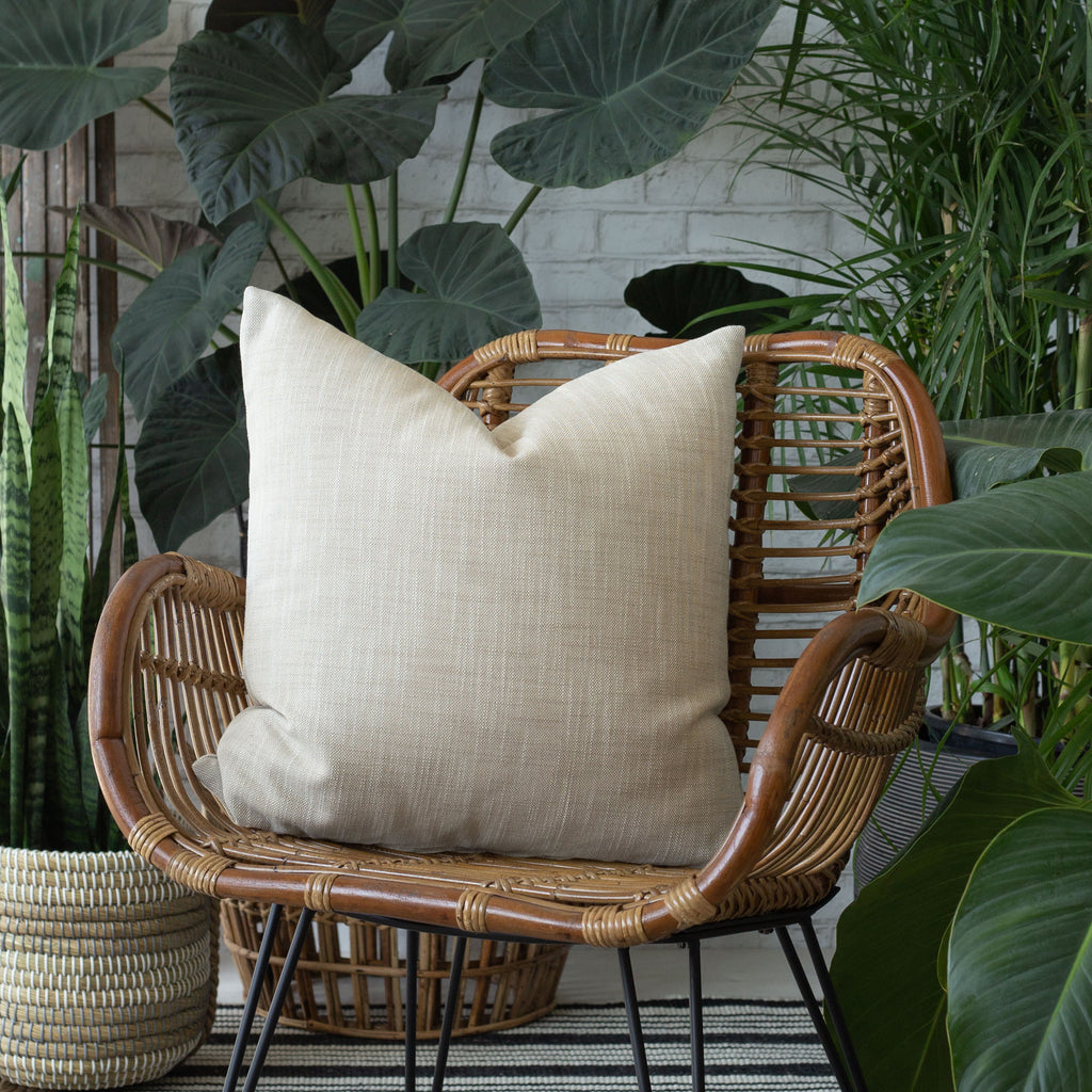 Ryder Swell beige pillow on a chair surrounded by plants