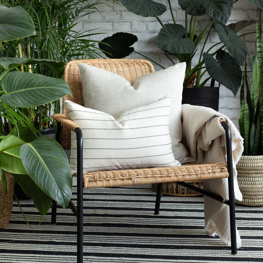 Indoor Outdoor decor vignette: Ryder Swell beige pillow with Fontana cream and black stripe lumbar pillow