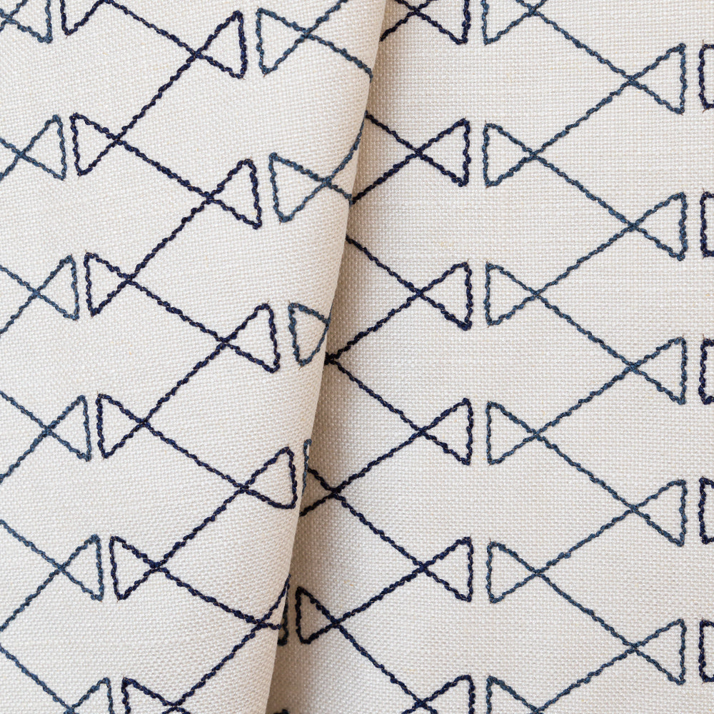 Santo blue graphic embroidery on ivory fabric from Tonic Living