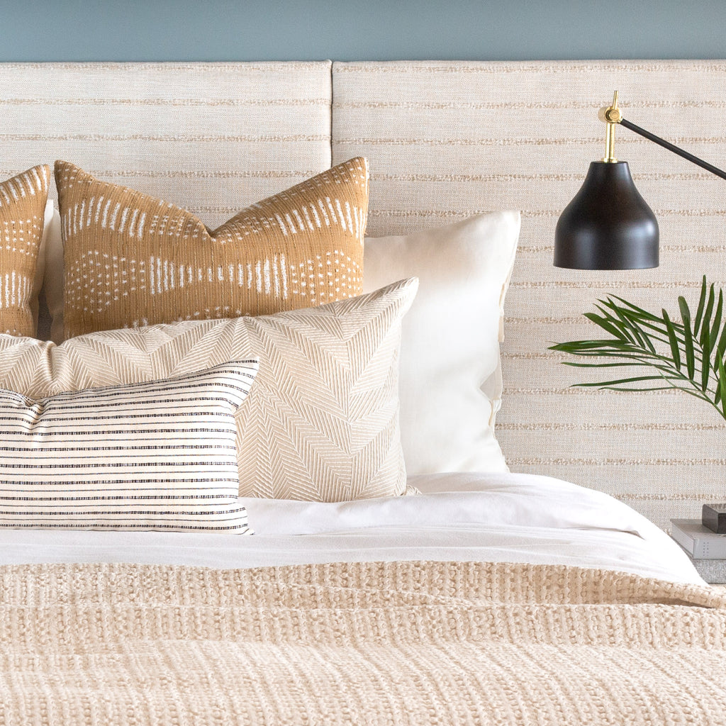 bed vignette: Zipporah cork pillows with Sardee beige embroidered bed bolster and misto cream and black lumbar pillow