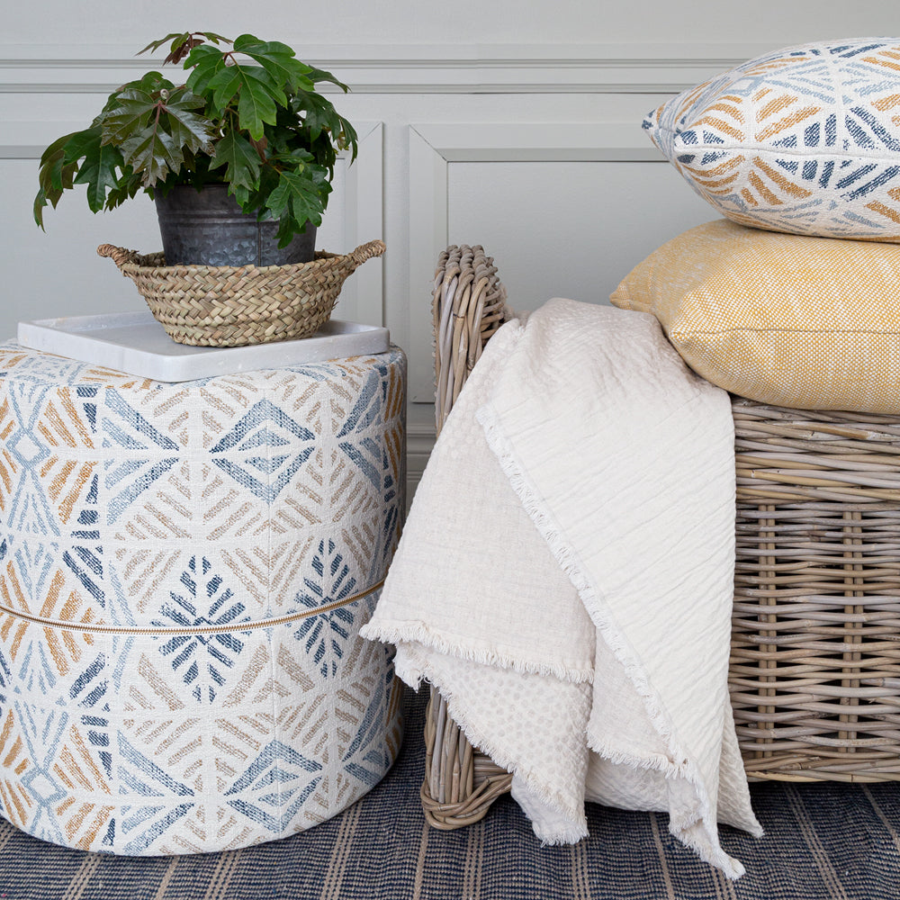Outdoor pillows and cream throw blanket from Tonic Living