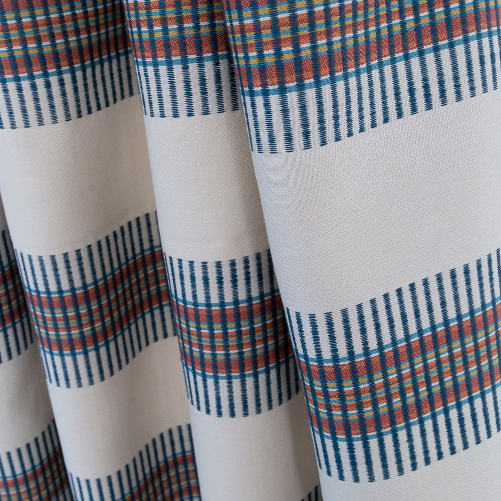 Zanzibar Regatta, a bold navy and rust horizontal global stripe on a light taupe fabric: close up view