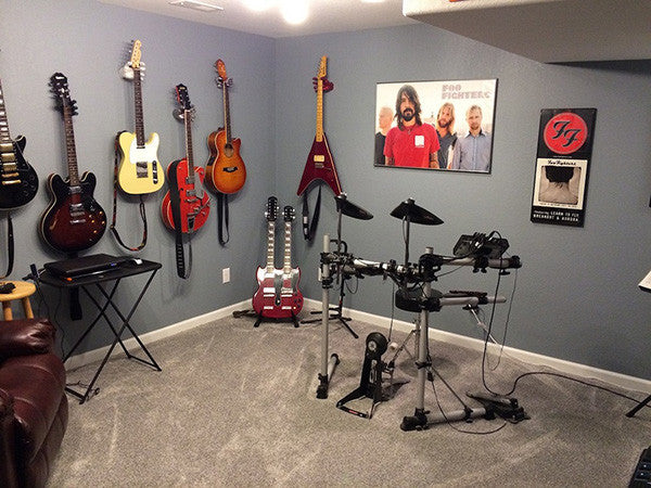 Music room with guitar wall display, black electronic drums set, and Foo Fighter poster.