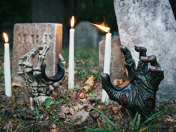zombie hand and skeleton hand guitar hangers sticking out of the ground in cemetery