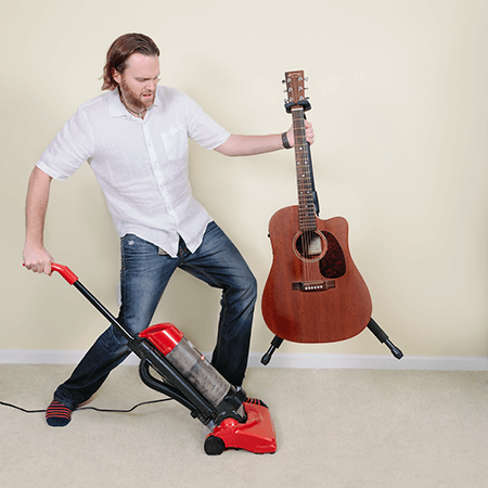 Man inconvenienced by having to lift up guitar and guitar stand to vacuum underneath.